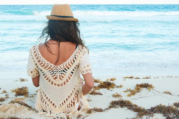 Linda mulher de chapéu na praia
