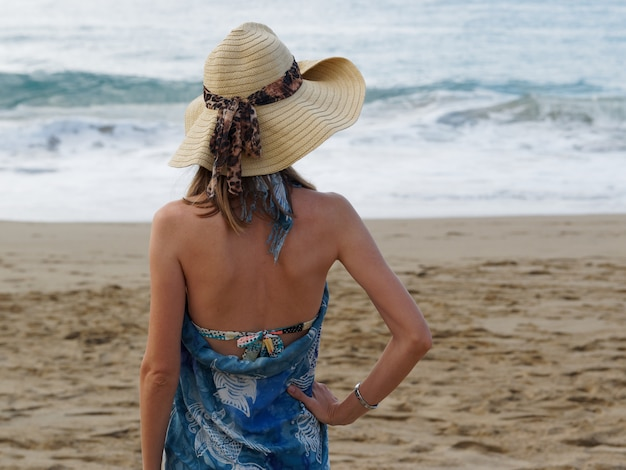 Linda mulher de chapéu na praia.