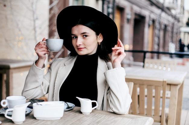 Linda mulher de chapéu preto hipster fedora desfrutando de café em uma loja de café