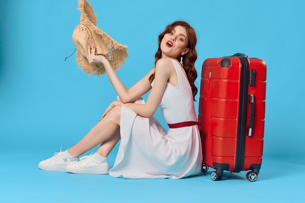 Linda mulher de chapéu, sentada no chão com destino de viagem mala vermelha. foto de alta qualidade