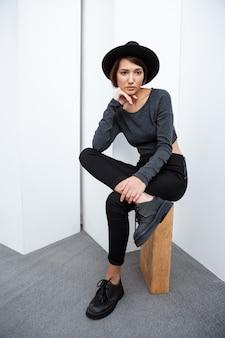 Linda mulher de chapéu, sentado na caixa