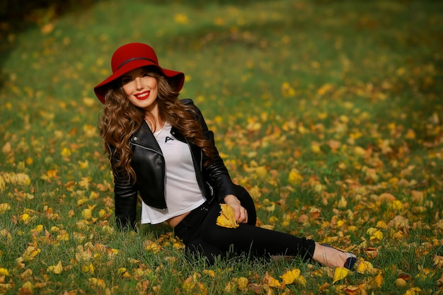 Linda mulher de chapéu vermelho sentada na grama do parque no outono