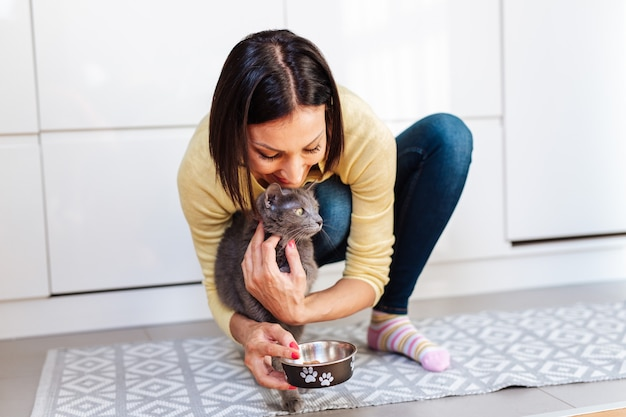 Linda mulher de meia-idade alimentando seu gato em casa.