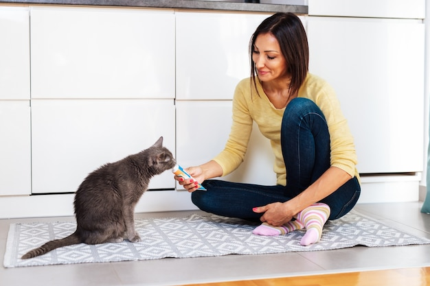 Linda mulher de meia-idade alimentando seu gato em casa