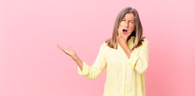 Linda mulher de meia-idade com boca e olhos bem abertos e mão no queixo
