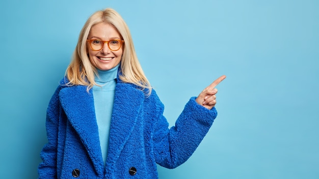 Linda mulher de meia-idade com cabelo loiro, usando óculos e um casaco azul quente apontando para o espaço da cópia