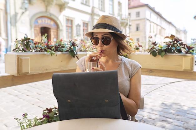 Linda mulher de meia-idade com óculos escuros, chapéu bebendo bebida gelada em um café ao ar livre de verão, mulher sentada sozinha, sorrindo olhando para longe