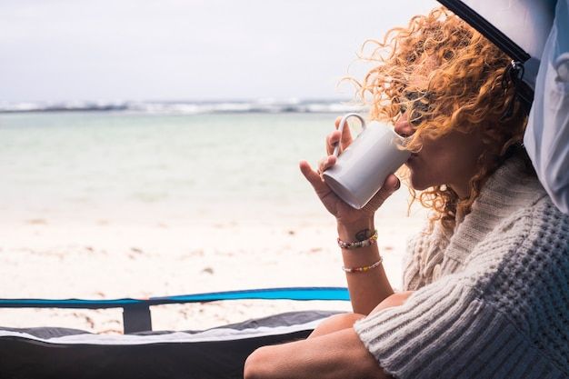 Linda mulher de meia-idade em acampamento gratuito dentro de uma barraca na praia de areia da costa do oceano, aproveitando férias alternativas - conceito de viagem de viagens e aventura para pessoas do estilo de vida moderno caucasiano