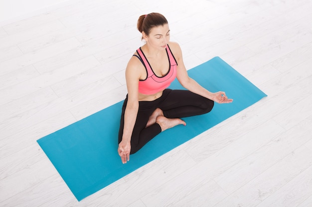 Linda mulher de meia-idade fazendo ioga dentro de casa. vista horizontalmente superior.