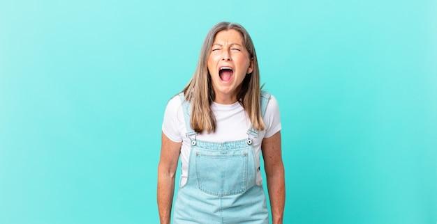 Linda mulher de meia-idade gritando agressivamente, parecendo muito zangada
