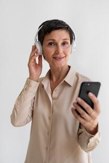 Linda mulher de meia-idade ouvindo música com fones de ouvido Foto Premium