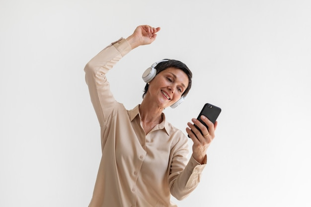 Linda mulher de meia-idade ouvindo música com fones de ouvido
