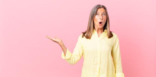 Linda mulher de meia-idade parecendo surpresa e chocada, com o queixo caído segurando um objeto
