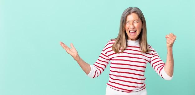 Linda mulher de meia-idade se sentindo chocada, rindo e comemorando o sucesso