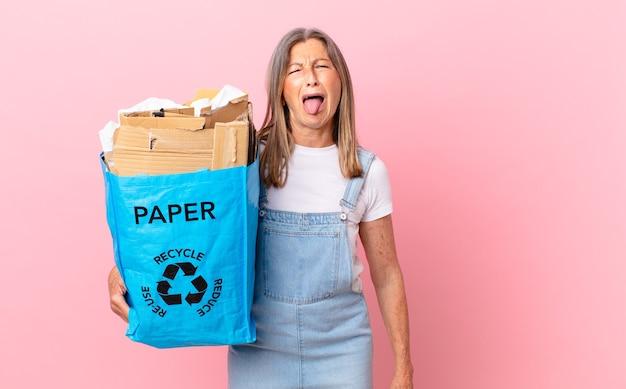 Linda mulher de meia-idade se sentindo enojada e irritada e com a língua de fora, reciclando o conceito de papelão