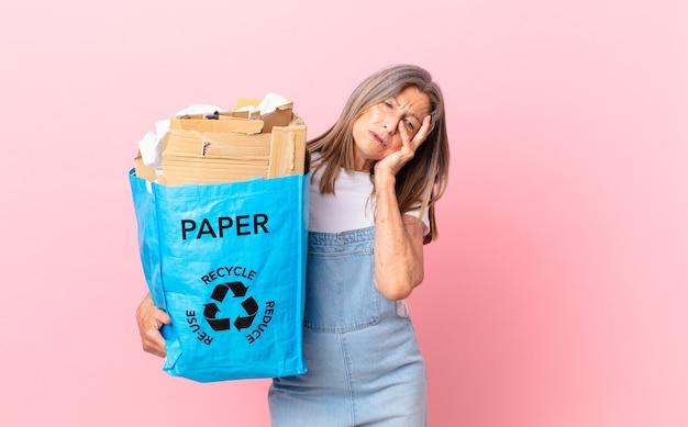 Linda mulher de meia-idade se sentindo entediada, frustrada e com sono após um cansativo conceito de reciclagem de papelão