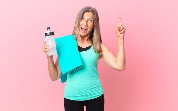 Linda mulher de meia-idade se sentindo um gênio feliz e animado depois de realizar uma ideia. conceito de fitness
