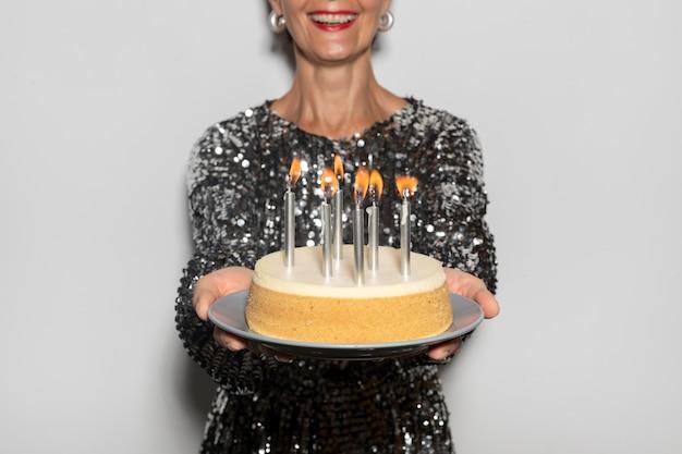 Linda mulher de meia-idade segurando um bolo de aniversário