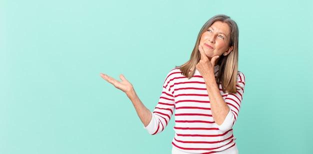 Linda mulher de meia-idade sorrindo com uma expressão feliz e confiante com a mão no queixo