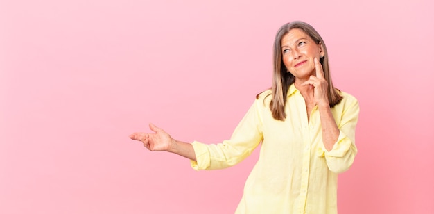 Linda mulher de meia-idade sorrindo feliz e sonhando acordada ou duvidando