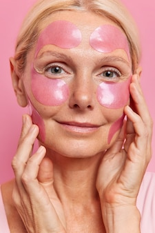 Linda mulher de meia-idade toca o rosto suavemente, tem tez saudável com adesivos colados e passa por procedimentos anti-envelhecimento aplica maquiagem mínima em poses internas reduz rugas, refresca a pele