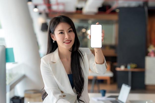 Linda mulher de negócios asiática olhando para a câmera segurando uma tela em branco do smartphone no escritório. brincar.