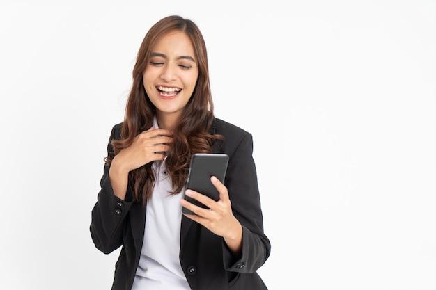 Linda mulher de negócios asiática sorrindo ao olhar para a tela do celular com espaço