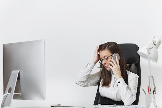 Linda mulher de negócios cansada e estressada de terno sentada à mesa, trabalhando no computador moderno com documentos em um escritório leve, falando no celular, resolvendo problemas