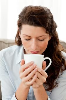 Linda mulher de negócios cheirando seu café sentado no sofá