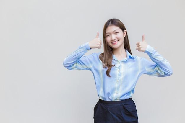 Linda mulher de negócios com cabelo comprido asiática com uma camisa azul, sorri e mostra o polegar para cima