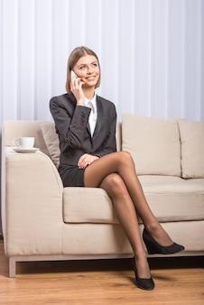 Linda mulher de negócios com café está falando por telefone.
