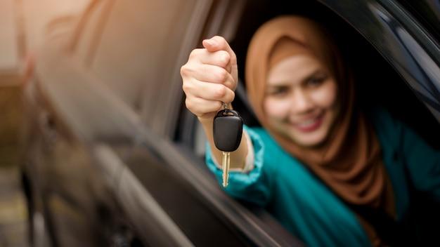 Linda mulher de negócios com hijab está sorrindo no carro dela