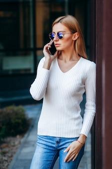 Linda mulher de negócios com óculos e telefone na rua