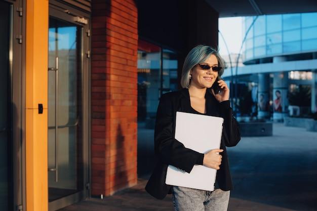 Linda mulher de negócios com óculos falando no telefone enquanto posa com um laptop