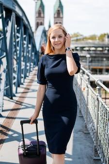 Linda mulher de negócios com saco grande, indo ao longo de uma ponte
