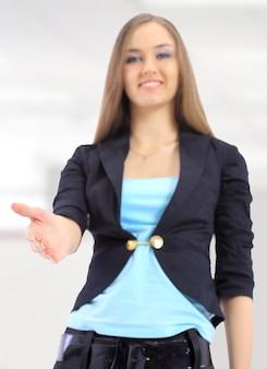 Linda mulher de negócios com uma proposta de aperto de mão no escritório.