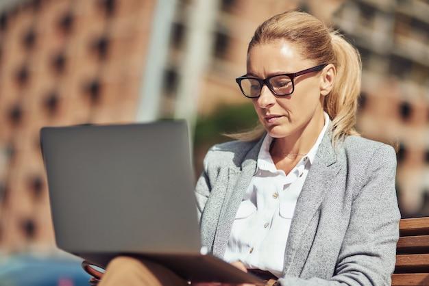 Linda mulher de negócios de meia-idade trabalhando on-line usando um laptop enquanto está sentado no banco