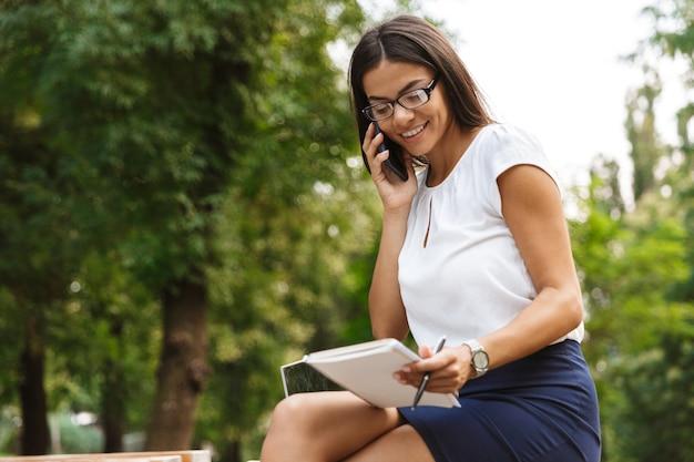 Linda mulher de negócios escrevendo notas falando ao celular