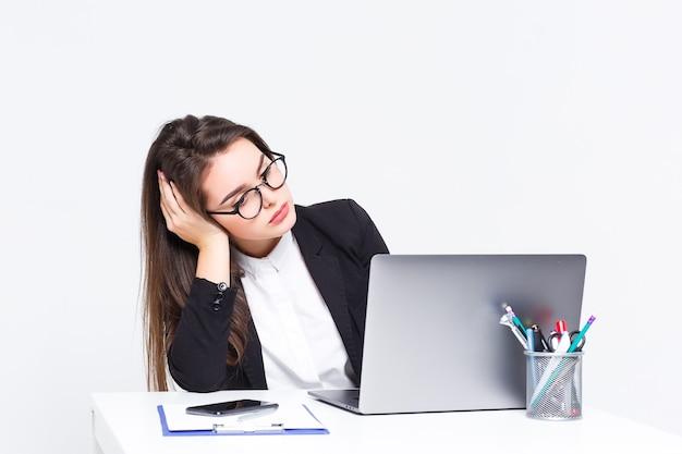 Linda mulher de negócios está muito cansada, ela está trabalhando com seu laptop cinza sobre fundo branco.