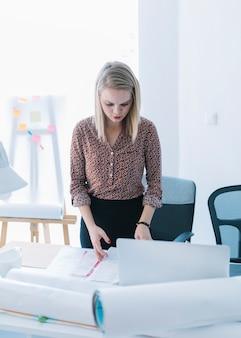 Linda mulher de negócios lendo o documento no escritório