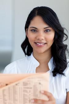 Linda mulher de negócios lendo um jornal