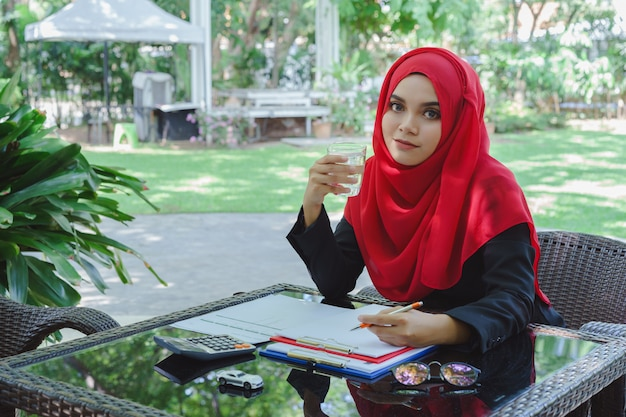 Linda mulher de negócios muçulmano vermelho hijab trabalhando ao ar livre e água potável