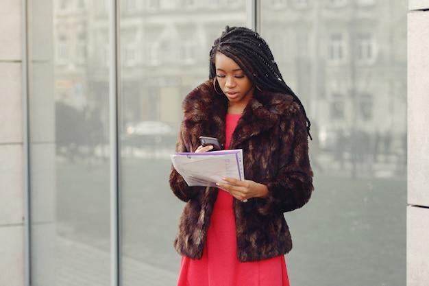 Linda mulher de negócios preto em uma cidade de primavera