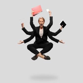 Linda mulher de negócios secretária multiarmed gerente levitando isolado no fundo cinza do estúdio