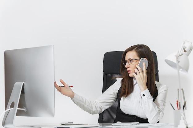 Linda mulher de negócios sérios de terno e óculos, sentada na mesa, trabalhando no computador contemporâneo com documentos em um escritório leve, falando no celular, resolvendo problemas.