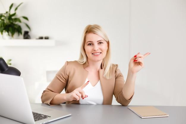 Linda mulher de negócios sorrindo sentada na mesa olhando para a câmera, apontar o dedo para a tela do laptop branco isolada sobre o fundo branco