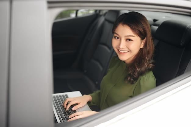 Linda mulher de negócios usando laptop enquanto está sentado no banco traseiro de um carro.