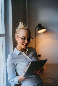 Linda mulher de negócios usando o tablet no escritório