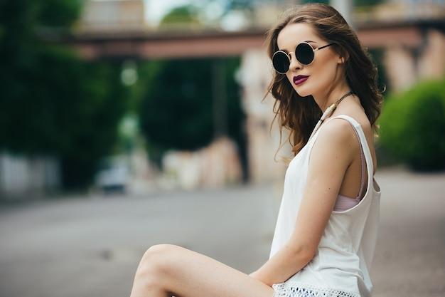 Linda mulher de óculos escuros sentada no asfalto