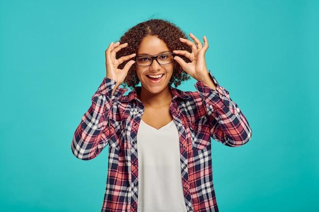 Linda mulher de óculos, parede azul, emoção positiva. expressão facial, pessoa do sexo feminino olhando para a câmera no estúdio, conceito emocional, sentimentos